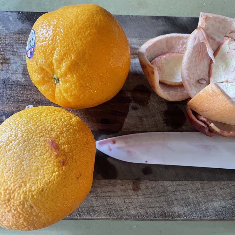 Oranges on cutting board with knife